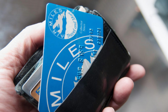 image of a man using his Air Miles rewards card to redeem Air Miles points before they expire on the redemption deadline date of January 1, 2017