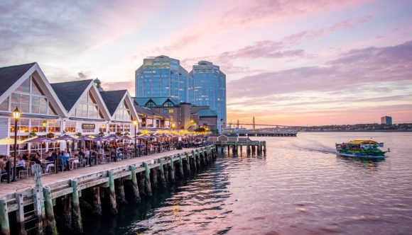 image of the Halifax Harbour Hopper Tour cruising by the Halifax boardwalk, one of the value-priced activities you can do while visiting Halifax