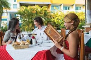 woman reviewing menu at one of the multiple restaurants to choose from at the cheap, all-inclusive Fiesta Americana Holguin Costa Verde resort in Cuba